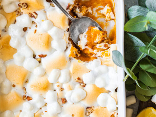 A picture of sweet potato casserole in a white baking dish topped with pecans and marshmallows